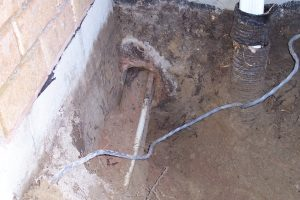 Basement leaking from around plumbing pipe penetrating foundation wall below ground