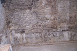 Older home with clear signs of water leakage through brick foundation walls